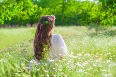 La muchacha con el pelo largo que lleva una corona de margaritas en el campo Fotografía de archivo libre de regalías