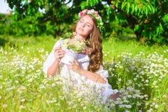 La muchacha con el pelo largo que lleva una corona de margaritas en el campo Fotografía de archivo