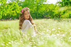 La muchacha con el pelo largo que lleva una corona de margaritas en el campo Imagenes de archivo