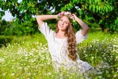 La muchacha con el pelo largo que lleva una corona de margaritas en el campo Foto de archivo libre de regalías