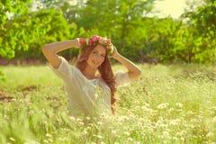 La muchacha con el pelo largo que lleva una corona de margaritas en el campo Fotos de archivo