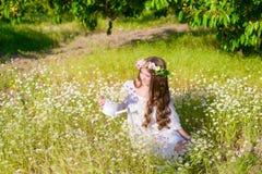 La muchacha con el pelo largo que lleva una corona de margaritas en el campo Imagen de archivo