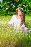 La muchacha con el pelo largo que lleva una corona de margaritas en el campo Fotos de archivo libres de regalías