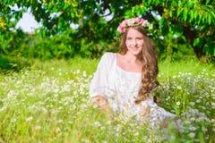 La muchacha con el pelo largo que lleva una corona de margaritas en el campo Foto de archivo