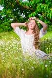 La muchacha con el pelo largo que lleva una corona de margaritas en el campo Imágenes de archivo libres de regalías