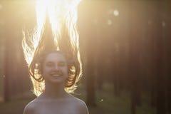 La muchacha con el pelo largo salta en bosque Fotografía de archivo