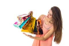 La muchacha con el pelo largo se coloca oblicua y los controles muchos regalos coloreados de los paquetes se aíslan de un fondo b Imagen de archivo