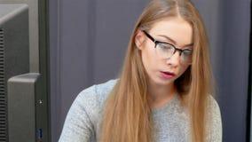 La muchacha con el pelo largo se está sentando delante del monitor, trabajando con los documentos, acabando a su mujer de negocio metrajes