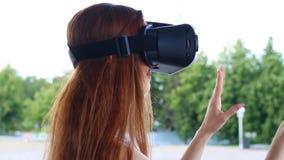 La muchacha con el pelo marrón largo al aire libre se divierte en vidrios de VR almacen de video