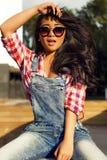 La muchacha con el pelo negro hermoso en gafas de sol se sienta Imagenes de archivo