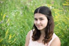 La muchacha con el pelo oscuro en fondo de la hierba verde Fotografía de archivo