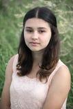 La muchacha con el pelo oscuro en fondo de la hierba verde Imagen de archivo