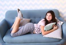 La muchacha con el pelo oscuro largo en pijamas pone en el sofá Foto de archivo