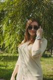 La muchacha con el pelo que fluye en gafas de sol mira en el marco, aumentando una mano a su cara fotos de archivo libres de regalías