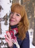 La muchacha con el pelo rojo en un bosque del abedul Imagen de archivo