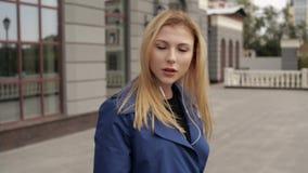 La muchacha con el pelo rojo escucha la música en la calle almacen de video