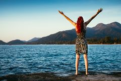 La muchacha con el pelo rojo está apreciando la visión maravillosa cerca del océano con las montañas y el bosque fotos de archivo libres de regalías