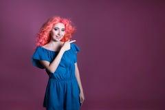 La muchacha con el pelo rosado en vestido azul muestra la muestra en el fondo de la lila, lugar para el texto Foto de archivo