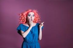 La muchacha con el pelo rosado en vestido azul muestra la muestra en el fondo de la lila, lugar para el texto Fotografía de archivo libre de regalías