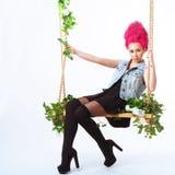La muchacha con el pelo rosado sacude en un oscilación Fotografía de archivo libre de regalías
