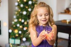 La muchacha con el pelo rubio hermoso en un vestido elegante lleva a cabo luces de la Navidad en sus manos y disfruta en la magia imagen de archivo