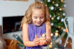 La muchacha con el pelo rubio hermoso en un vestido elegante lleva a cabo luces de la Navidad en sus manos y disfruta en la magia fotografía de archivo