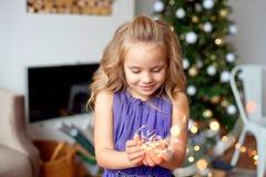 La muchacha con el pelo rubio hermoso en un vestido elegante lleva a cabo luces de la Navidad en sus manos y disfruta en la magia foto de archivo