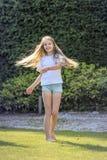 La muchacha con el pelo rubio largo baila en el jardín en un día de primavera hermoso y es alegre Fotografía de archivo libre de regalías