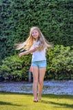 La muchacha con el pelo rubio largo baila en el jardín en un día de primavera hermoso y es alegre Foto de archivo