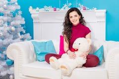 La muchacha con el peluche blanco refiere un sofá foto de archivo