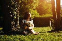 La muchacha con el perro se sienta en una hierba Fotos de archivo libres de regalías