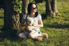 La muchacha con el perro se sienta en una hierba Imágenes de archivo libres de regalías