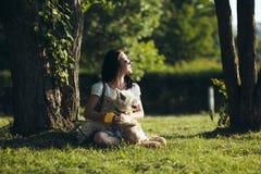 La muchacha con el perro se sienta en una hierba Imagen de archivo libre de regalías