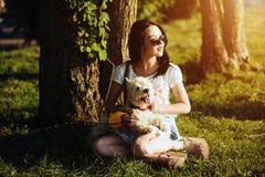 La muchacha con el perro se sienta en una hierba Fotos de archivo