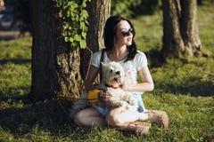 La muchacha con el perro se sienta en una hierba Foto de archivo libre de regalías