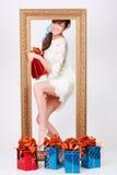 La muchacha con el rectángulo con el regalo sale del marco de la cerda joven fotografía de archivo libre de regalías