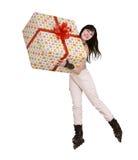 La muchacha con el rectángulo de regalo va a patinar. Fotografía de archivo