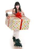 La muchacha con el rectángulo de regalo va a patinar. Fotos de archivo