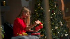 La muchacha con el sombrero de la Navidad hace deseos y abre un paquete del regalo de la Navidad Concepto de días de fiesta y de  almacen de video