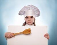 La muchacha con el sombrero del cocinero indica Foto de archivo libre de regalías