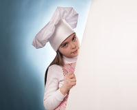 La muchacha con el sombrero del cocinero indica Fotos de archivo