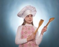 La muchacha con el sombrero del cocinero indica Imágenes de archivo libres de regalías