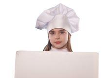 La muchacha con el sombrero del cocinero indica aislado con las carteleras Fotos de archivo