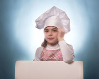 La muchacha con el sombrero del cocinero indica aislado con las carteleras Imagen de archivo