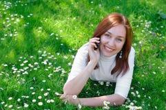 La muchacha con el teléfono en la hierba Fotos de archivo libres de regalías