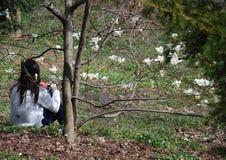 La muchacha con el teléfono móvil se sienta debajo de árbol con las flores florecientes de la magnolia blanca Imagenes de archivo