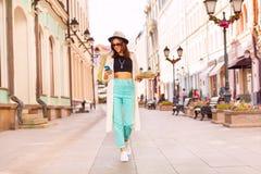 La muchacha con el teléfono móvil y la ciudad trazan en la calle Imágenes de archivo libres de regalías