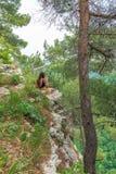 La muchacha con el teléfono se sienta en una roca rodeada por los pinos verdes fotos de archivo