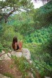 La muchacha con el teléfono se sienta en una roca rodeada por los pinos verdes imagenes de archivo