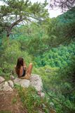 La muchacha con el teléfono se sienta en una roca rodeada por los pinos verdes fotos de archivo libres de regalías